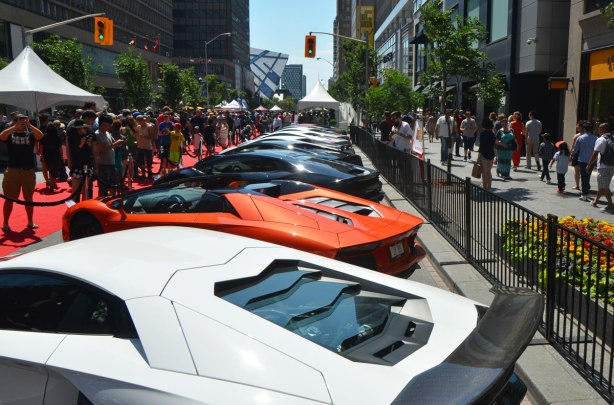 Several lamborghinis parked beside each other on Bloor Street as part of the Yorkville exotic car show. Lots of people are looking at them.