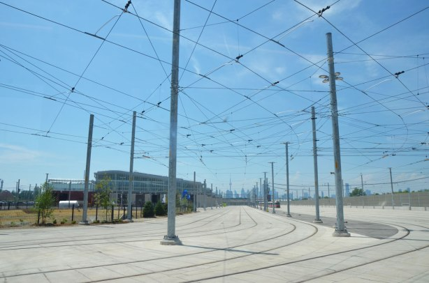 the massive concrete parking lot for streetcars with all the overhead wires. The building that houses the workshops and cleaning and office for the ttc is in the background.