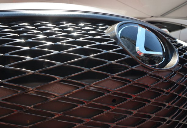 close up of the front grille of a Lexus car showing the L Lexus symbol and the diamond pattern of the metal work.