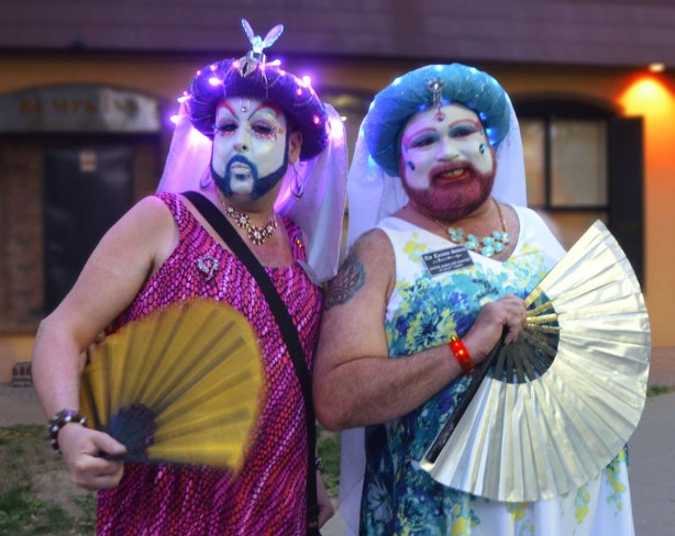Two guys in drag with lights all over their costume, holding large fans
