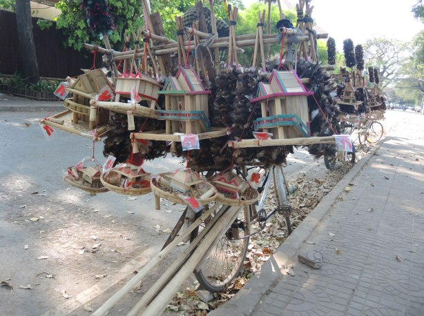 two bicycles laden with small wooden model houses that are for sale
