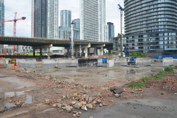 construction site in downtown Toronto, Gardiner Expressway runs behind the site, rubble in the foreground, a few remaining remnants of the old Loblaws building that was there, high rises in the background.