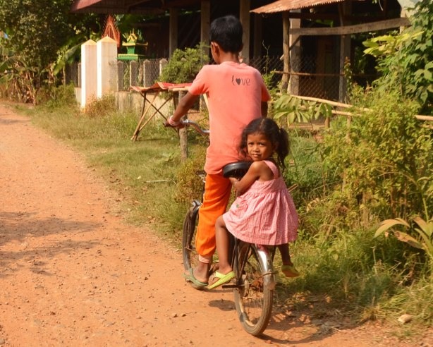 a young girl sits on the back fender of a bike ridden by a boy. She is wearing a pink dress and she is looking back at the camera. The boy is dressed in orange and only the back of him can be seen
