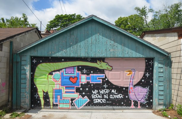 "mural on a garage door in an alley. a green giraffe, a blue lovebot, and a purple goose, with the words ""We were all born in outer space"""