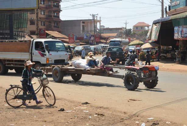 a couple drives a vehicle that is made of a truck chassis and four wheels, no body, through an intersection