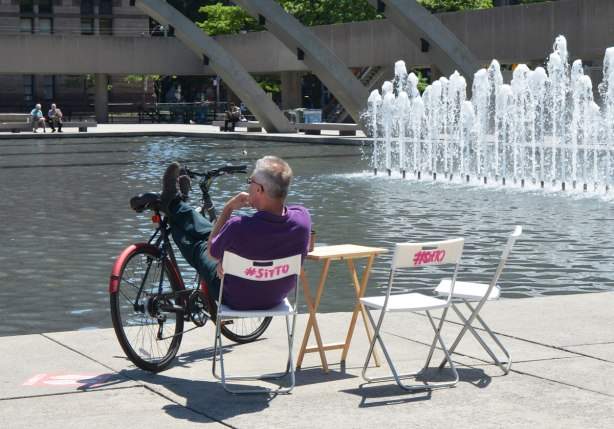 A man sits on a folding chair beside the fountain at Nathan Phillips Square. He has his feet up on the bars of his bike that is balanced there.
