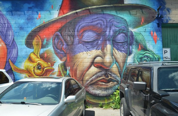 mural of a man's face, eyes closed, wearing a hat, mustache, older man