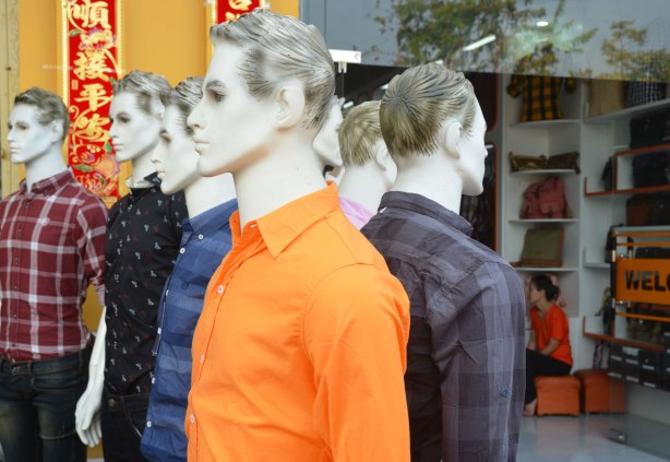 Two lines of white mannequins with black and white hair painted on, modelling men's shirts, in front of a store