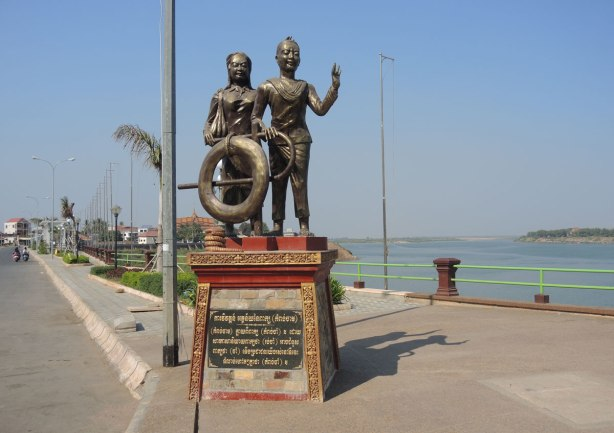 a bronze statue beside the Mekong River of a couple standing together with a life ring and a lifesaving hook