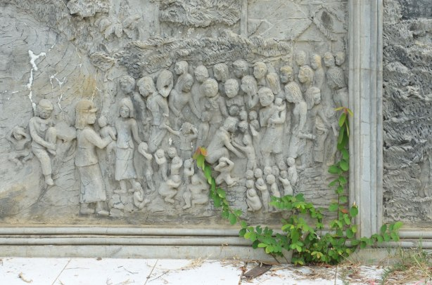 bas relief sculpture of children being taken from their parents during the Khmer Rouge regime, in stone, bottom part of a memorial stupa