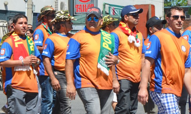 men, members of a Labour Union, walk in a parade. They are wearing orange shirts with short blue sleeves that say Portugal Day on them.