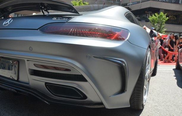 silver mercedes gts car, viewed from behind the back passenger side wheel, parked on Bloor St. for a car show. Some people in the background.
