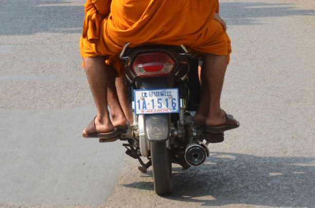 from the back, three or four monks in orange robes riding on the same motorcycle.