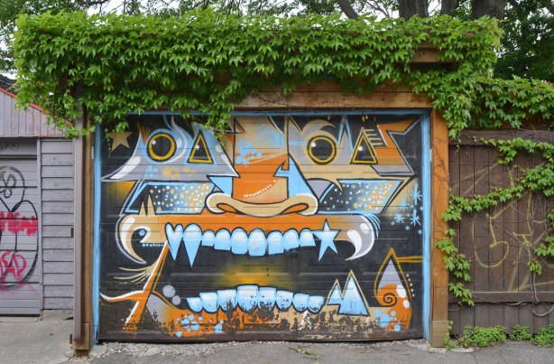 garage door painted with a monster face, big mouth and teeth, orange nose, in tones of blue, grey and orange, ivy is growing over the top of the garage and it looks like green hair.