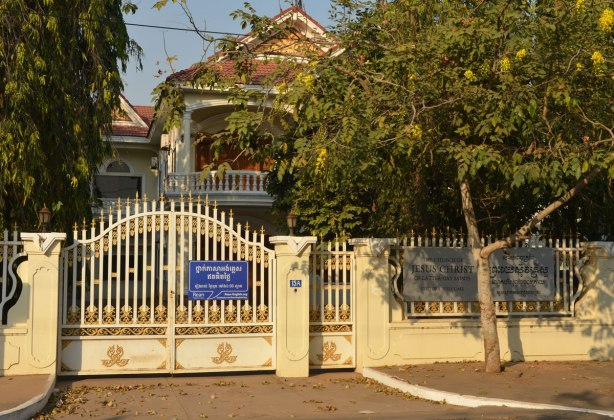 the exterior of the church of latter Day Saints (Mormons) behind a gate and trees in Cambodia. Looks like a house, yellow fence and gate