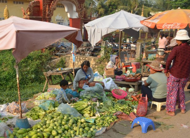 A group of people, women and children, selling vegetables beside the road.
