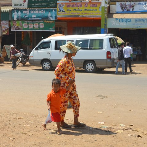 a mother and son, both dressed in orange clothes, walk along the side of a road. A white van is in the background.