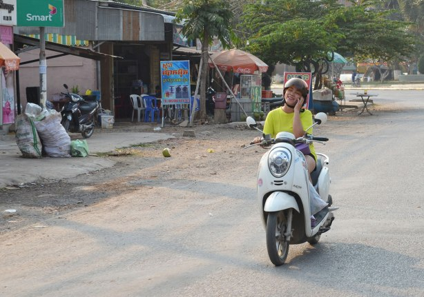a teenage girl rides a motorcycle while talking on her cellphone and laughing