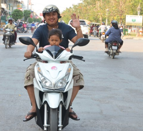 A father and daughter on a motorcycle. The girl is in front. The man is waving.