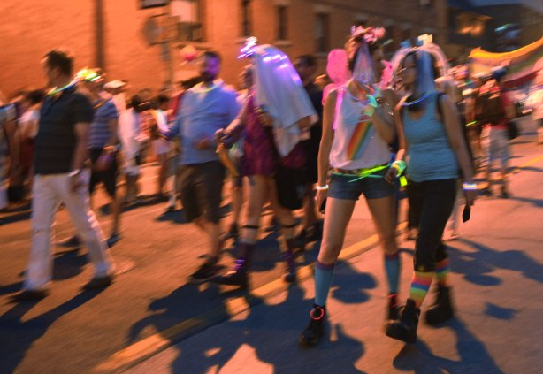 people walking in a parade, glow sticks, some costumes, a woman with pink butterfly wings