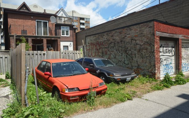 two old cars, one red and one dark grey, are parked in an overgrown backyard on an alley.