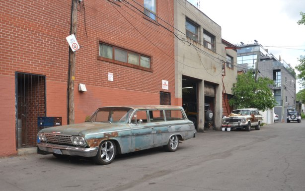 wide lane behind Dupont Street in Toronto, an old car is parked there, back of an auto repair shop, sturdy looking two storey brick buildings.