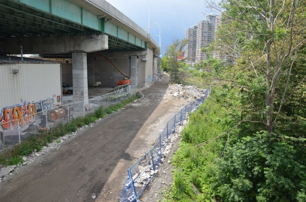 a dirt road runs alongside the Gardiner Expressway, some condos in the distance