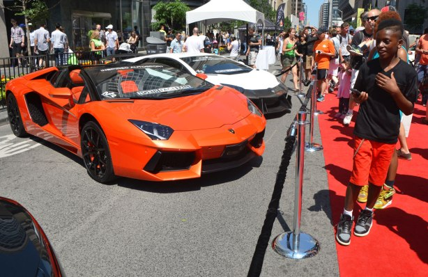 a boy walks past an orange lamborghini