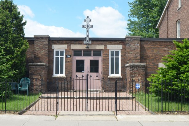 low, one storey brick building with a pink double door, metal fence and gate in front, ornate cross above the door.