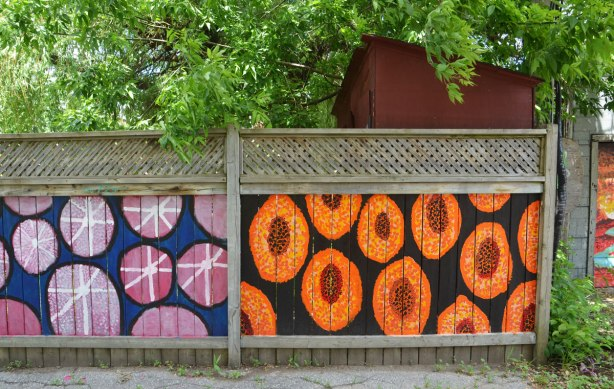 two sections of wooden fence painted, one with pink circles and the other with orange ovals