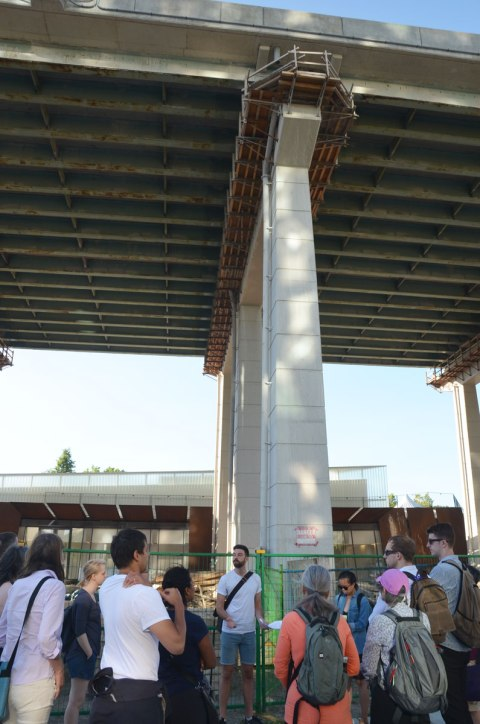 a man is standing in front of a group of people on a walking tour, he is standing under the Gardiner Expressway where it is 5 storeys above ground level.
