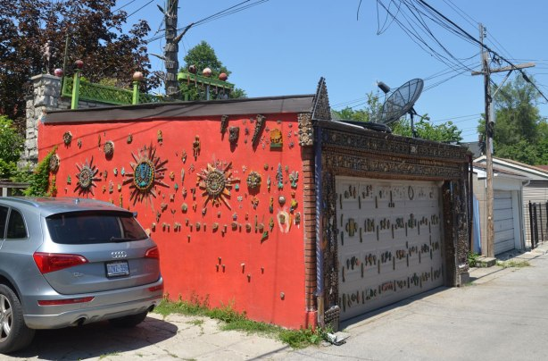 garage in a laneway decorated by Albino Carreira using slices of wood, pool cues, toy figures, and small found objects - one side of the garage is painted red and covered with decorations