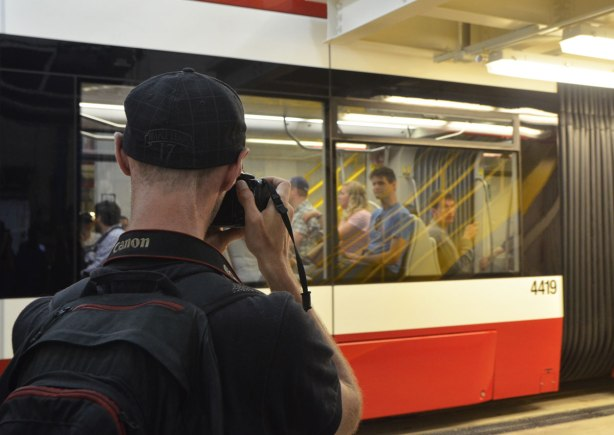 A man in black T-shirt and black cap is taking a picture of people riding in the new streetcar, inside Leslie Barns at Doors Open