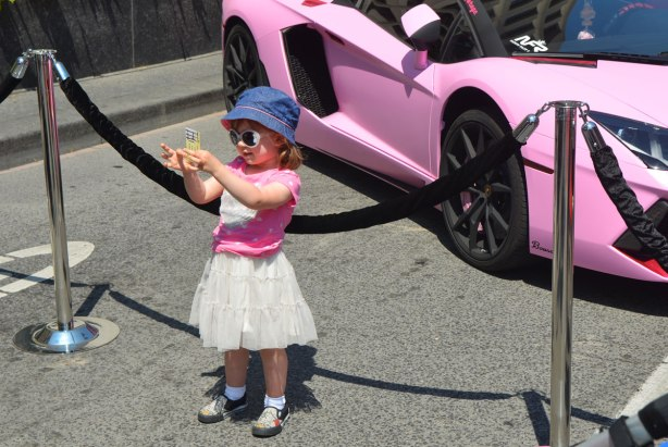 A little girl in white skirt, pink T-shirt, blue hat and big sunglasses stands in front of a fancy pink car at an outdoor car show