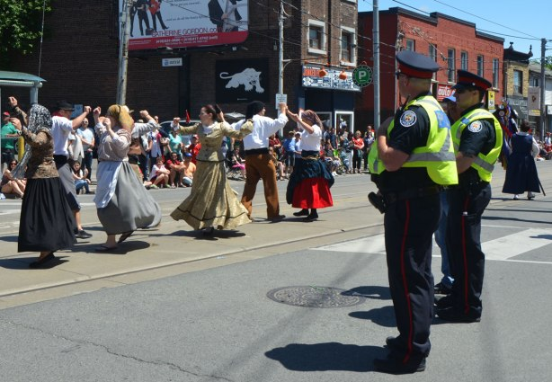 Two Toronto policemen in yellow safety vests watch a parade, women dancing past them.