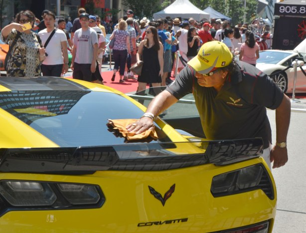 a man in a black short sleeve shirt and a yellow baseball cap is cleaning and polishing the rear window of a yellow Corvette at a car show, lots of onlookers in the background.