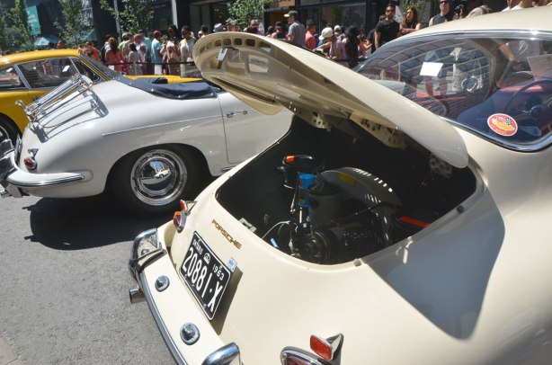 two older classic Porsches, both white, parked in a car show, the one in the foreground has its trunk open to show the engine in the back of the car. Lots of people looking at the cars