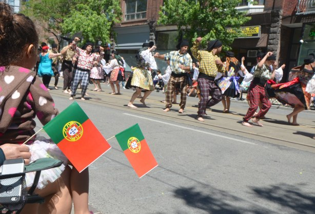Spectators in a parade hold small Portuguese flags as they watch traditional dancers perform.