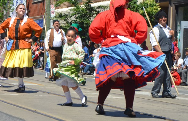 A young girl swirls her long skirt as she dances in a parade. Portugal Day parade on Dundas West, Little Portugal, in Toronto