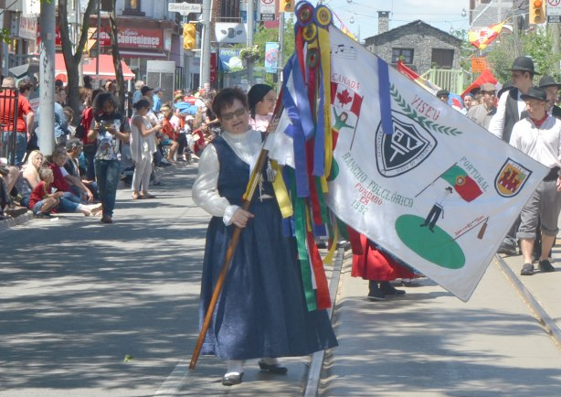 A woman holds a colourful banner in a parade