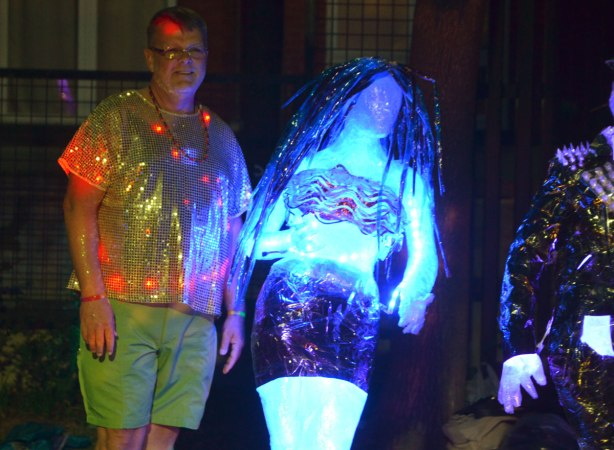 a man with lights in his shirt poses beside two statues that light up