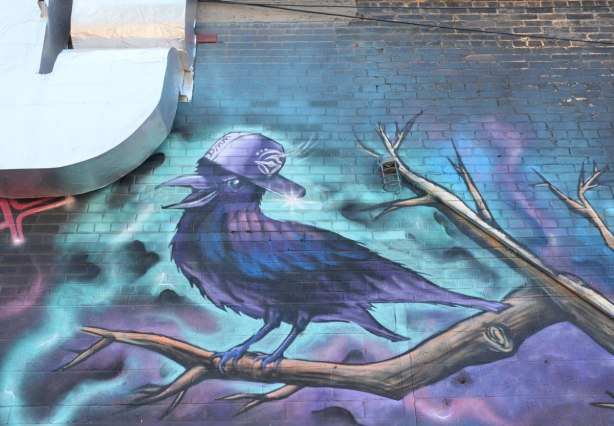 a blue and purple bird sings while standing on the branch of a tree, it's wearing a baseball cap. Part of a mural