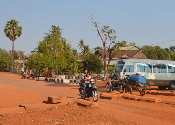 a man and a boy on a motorcycle on a red dirt road.
