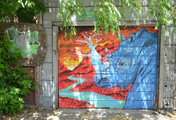 graffiti street art animals painted on garage door in an alleyway - a blue rhinoceros with a horn that looks like a tree