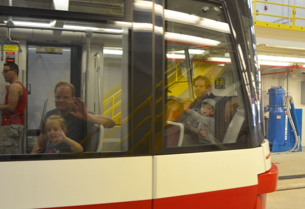 people riding in a new streetcar, photo taken from the outside, most of them are waving