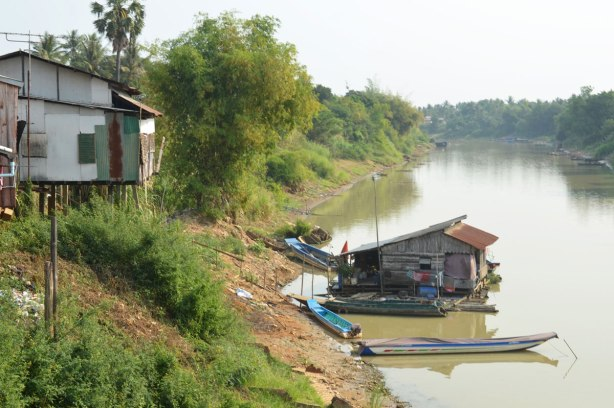 river, on the riverbank is a house on wood stilts, at river level is another house that is floating on the water. Two flat boats are docked by it.