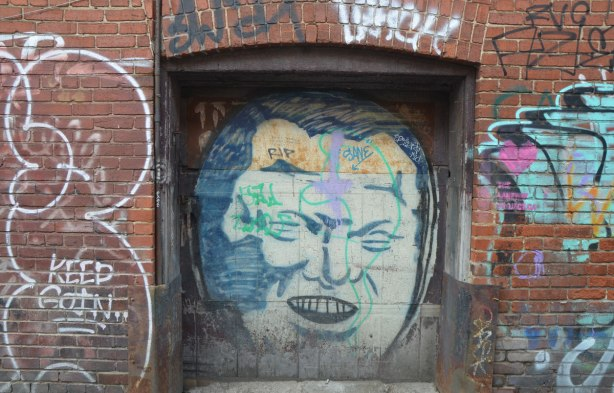an old doorway in a red brick building in a lane. There is an old graffiti face of Rob Ford painted on the door. R I P has been written on his forehead.