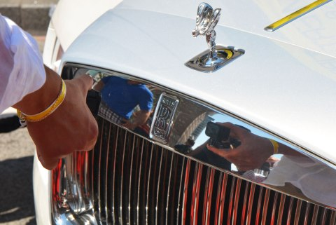 a person using a GoPro to take a picture of reflections in the chrome on the front of a Rolls Royce