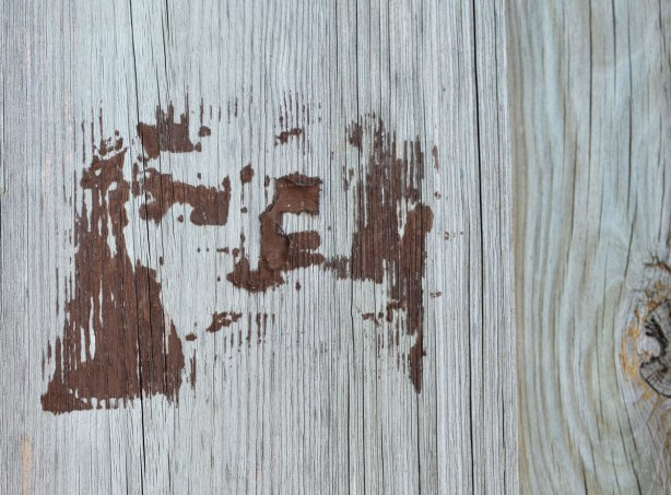 a brown stencil of a man's face on a wood fence but the paint was a bit heavily applied and there are some paint blobs