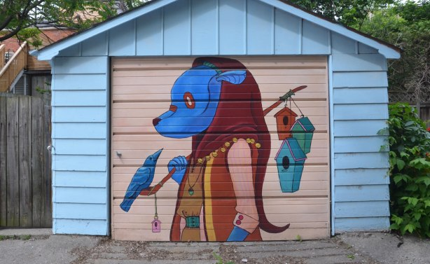 blue faced animal wearing clothes and walking upright, with pole over shoulder, 3 bird houses hanging from the pole. A bluebird is sitting on the front of the pole, mural on a garage door in a lane